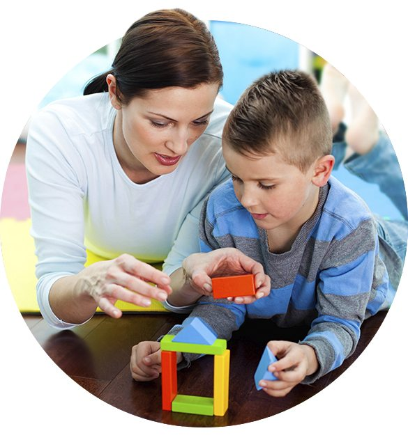 Female playworker helps a young boy with building blocks